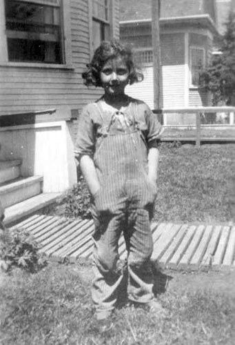 PK as child standing in front of house