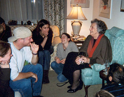 Elderly PK sitting in livingroom with young adult students